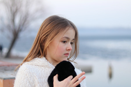 Pretty little pensive girl looking thoughfully to the right holding her soft toy and counting on her fingers, close up, outdoors Stock Photo
