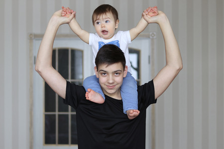 Happy smiling teenager boy holding his little brother sitting on his neck Stock Photo