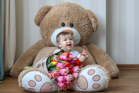 Cute little baby smiling with his first four teeth, sitting on huge teddy bear with big bouquet of tulips