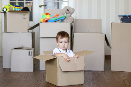 Cute little baby boy sitting inside cardboard box with big boxes full of toys on background, moving out concept