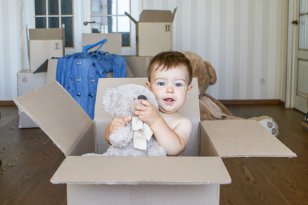 Cute little baby boy inside cardboard box holding and packing his toy teddy bear in the room with big boxes on background, moving out concept