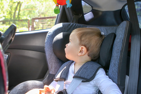 Cute little baby boy in car safety seat looking at the window. Traveliing with child and baby transportation safety concept