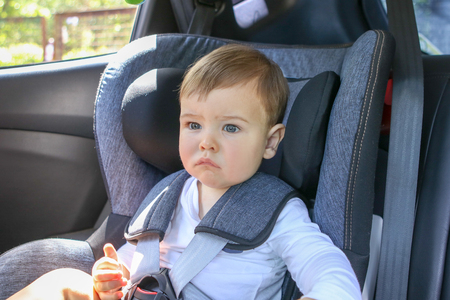 Portrait of cute little thoughtful baby sitting in the baby car seat looking forward. Traveling with child abd baby safety concept. Little passenger transportation