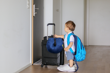 Funny little baby boy in fathers shoes with big backpack, suitcase and spoon in his hand staying in hallway looking at door ready to leave, prepared for travel.  Child traveling concept