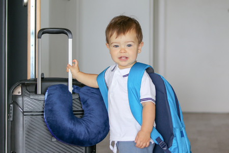 Close-up portrat of cute smiling little baby boy with big backpack and suitcase with travelling pillow stay near open door ready to leave, prepared for travel. Traveling with child concept