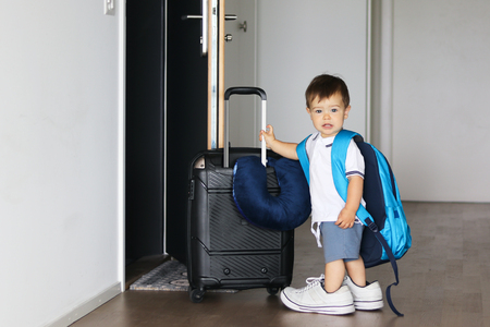 Cute little baby boy in fathers shoes and with big backpack holding suitcase staying near open door ready to travel leaving home. Traveling with child concept Stock Photo