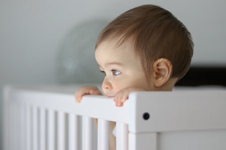 Close-up portrait of cute thoughtful baby staying in his baby cot holding the side and daydreaming, looking outside