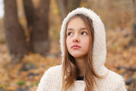 Close-up portrait of beautiful thoughtful dreaming little girl in white hoody coat staying in autumn forest, outdoors