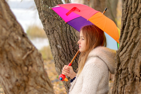 Beautiful little girl with rainbow colored umbrella dreaming staying near the tree outside looking into the distance