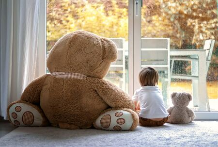 Watching autumn rain. Little boy sitting with his big and little soft teddy bear friends on carpet in front of window looking outside. Fall lifestyle. Frendship. Seasonal mood Stock Photo