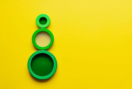 Geometry. Three green circles on bright yellow background. Minimalism. Creative abstract tree concept. Educational wooden toys for children, learning shapes and colours