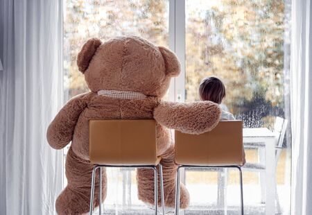 Watching autumn rain. Little boy sitting with his big soft teddy bear friend on chairs ion front of window looking outside. Fall lifestyle. Frendship. Seasonal mood