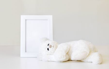 Mockup. Soft white little teddy bear toy sleeping near white clean mock up frame with copy space at light grey background. Empty space. Baby children concept.