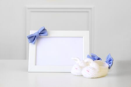 Mock up.  White empty frame with little baby blue checkered bow tie and knitted baby bootiesat light grey background. Copy space. Newborn baby boy concept.  Stock Photo