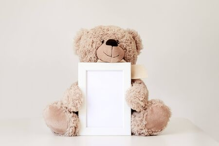Mockup. Soft beige teddy bear toy holding white clean mock up frame with copy space sitting at light grey background. Empty space. Baby children concept.