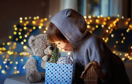 Christmas mood. Cute little excited child with teddy friend looking inside gift box with christmas toys and light from it with garland lights bokeh at background at home.   Stock Photo