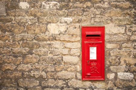 buzon: moda Inglés buzón rojo tradicional viejo montado en una pared de piedra de Cotswold Foto de archivo