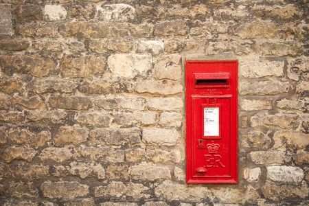 traditional old fashioned English red postbox mounted in a cotswold stone wall Stock Photo