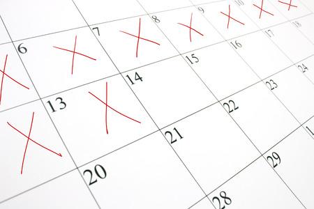 cruz roja: Close up de una p�gina de calendario blanco con algunos de los d�as tachados con una X roja