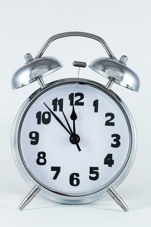 top 7: old style silver alarm clock with hammer and bells on top with hands at 7 minutes to midnight Stock Photo