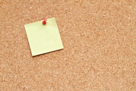 blank post it note pinned to a cork board  bulletin board