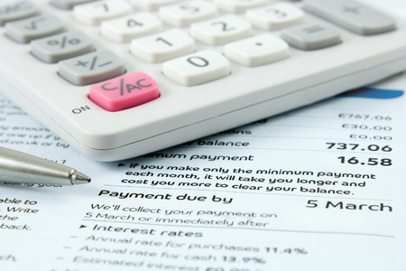 bank statement: calculator and silver ballpoint pen sitting on a bank statement with focus on the payment due date Stock Photo