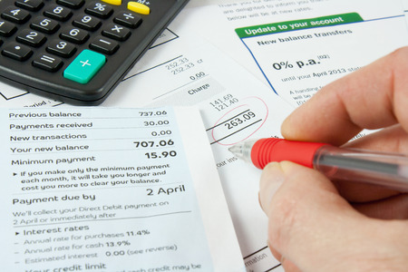 account statements: a persons hand holding a red pen and checking bankstatements with a calculator Stock Photo