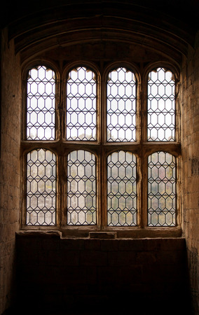 norman castle: interior view of sunlight shining through a stone arched window of an ancient Norman castle Editorial