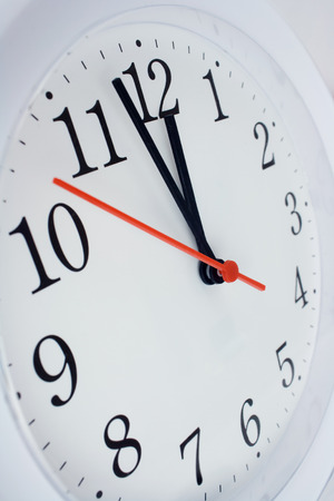 12 oclock: close up of a clock face showing the hands at two minutes to midnight Stock Photo