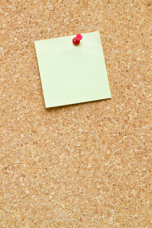 bulletin: blank post it note pinned to a cork board  bulletin board