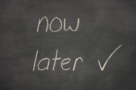later: now later written on a blackboard with the word later ticked
