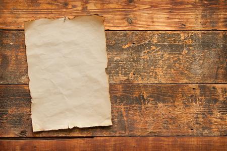 close-up van een oude versleten blanco stuk papier met verbrande en gescheurde randen genageld aan een oude verweerde plank deur