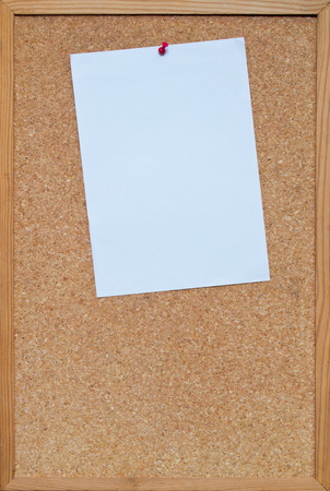 blank piece of A4 paper pinned to a  cork board  bulletin board with a wooden frame