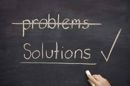 problems solutions: problems  solutions written on a blackboard  chalkboard with the word problems crossed out and solutions underlined.