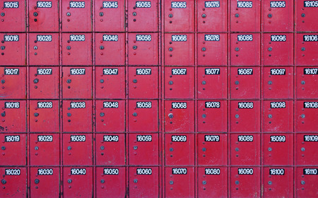 chipped paint: rows of old red post office boxes with with chipped paint