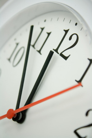 clock hands: close up of a white clock face showing the hands at just before twelve