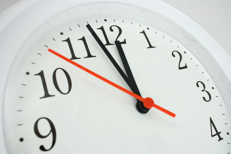 12 o'clock: close up of a clock face showing the hands at two minutes to midnight Stock Photo