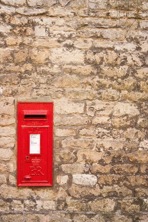 cotswold: traditional old English red postbox mounted in a cotswold stone wall