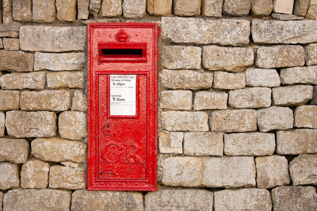 cotswold: traditional old fashioned English red postbox mounted in a cotswold stone wall Stock Photo