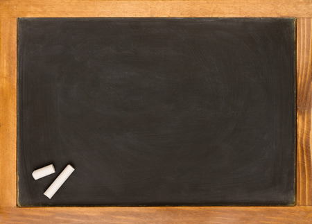 blank slightly dirty chalkboard with an old pine frame two pieces of chalk in one corner Stock Photo