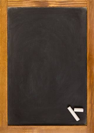 verticales: Pizarra en blanco ligeramente sucio con un marco de pino viejo dos pedazos de tiza en una esquina Foto de archivo