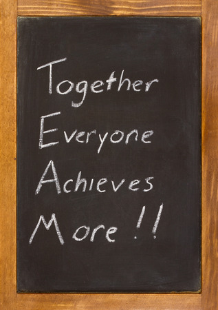 chalk board background: Small chalkboard with a wooden frame with together everyone achieves more written on it in white chalk.