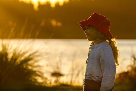and four of the year: close up of a four year old child wearing a bright red hat  standing on the shore of a lake at sunset