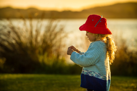 caucasion: close up of a a four year old child wearing a bright red hat  playing happily at sunset on the shore of a lake