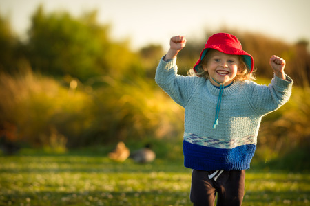 and four of the year: a four year old child wearing a bright red hat running happily at sunset in the park. Stock Photo