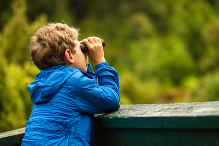 close up of a young boy in a blue coat looking through binoculars at birds with a blurred green background Stock Photo