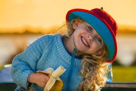 close up of a smiling child wearing a hat and holding a half eaten banana at sunset
