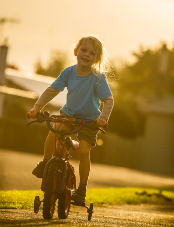 young child riding a bike with trainer wheels at sunset