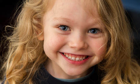 close up of a 4 year old child with blonde hair and blue eyes happily smiling up at the camera Stock Photo