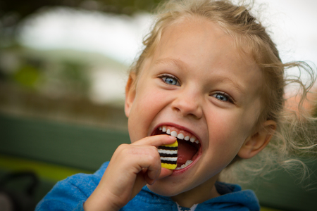 blonde haired: close up of a young blonde haired blue eyed child with mouth wide open about to eat a large sweet.